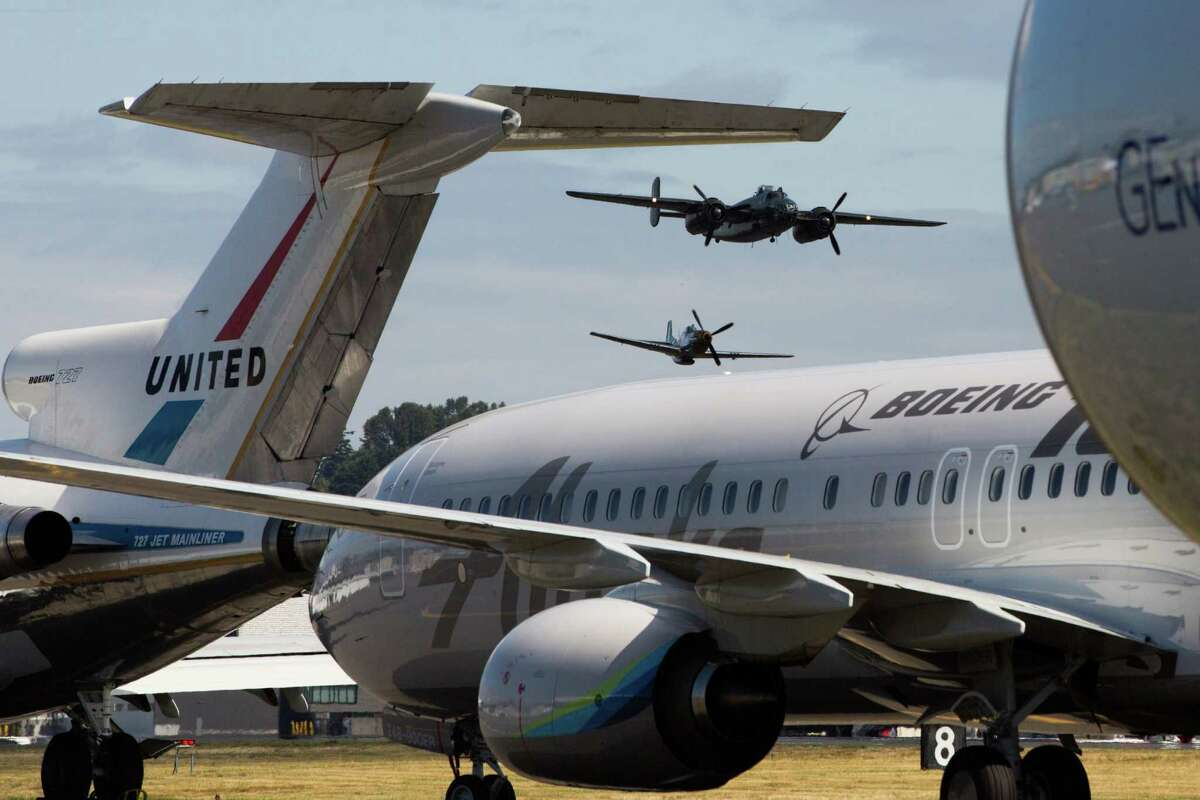 Historic planes do laps past a lineup of Boeing 7-series planes during at an event marking Boeing's 100th anniversary, at Boeing Field in Seattle on Friday, July 15, 2016.