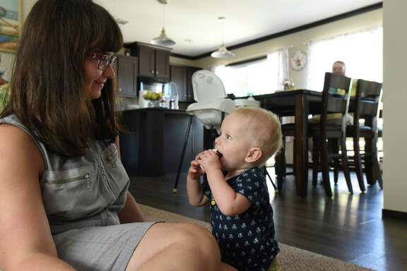 Hanna Nowak and her 1-year-old son, Bill, enjoy a moment at their home in Floresville. Hanna and her husband, Damian Nowak, currently pay almost $700 a month for a Blue Cross Blue Shield of Texas health insurance plan.