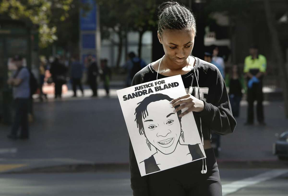 Laelah Jackson holds a picture of Sandra Bland a victim of police brutality, during a Black Lives Matter protest at the intersection of Broadway and 14th streets in Oakland, California, on Fri. July 15, 2016.