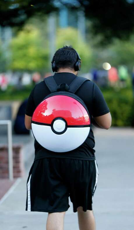 """Henry Morales walks and plays Pokemon Go, with a Pokemon backpack in Discovery Green, which is a """"gym"""", a place where Pokemon players can battle for ownership, Wednesday, July 13, 2016, in Houston.  Gyms attract more players to them, more than other parts of the city, where hundreds have been showing up each night since the Pokeman app started, last week.  ( Karen Warren  / Houston Chronicle ) Photo: Karen Warren, Staff / © 2016 Houston Chronicle"""