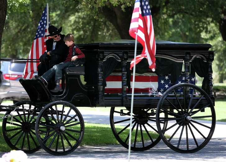 Magnus Ahrens, 8, son of fallen Dallas police Senior Cpl. Lorne Ahrens, rides with the driver of a caisson bearing his father's casket.  (Rose Baca/The Dallas Morning News)