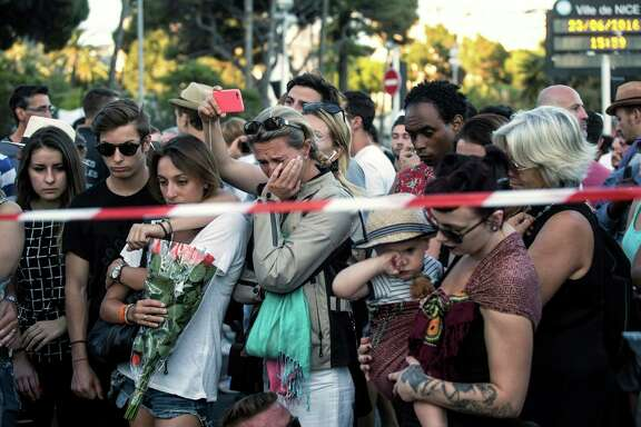 People react as they gather at a makeshift memorial to honor the victims of an attack in Nice, France, Friday. A large truck mowed through revelers gathered for Bastille Day fireworks, killing more than 80 people.