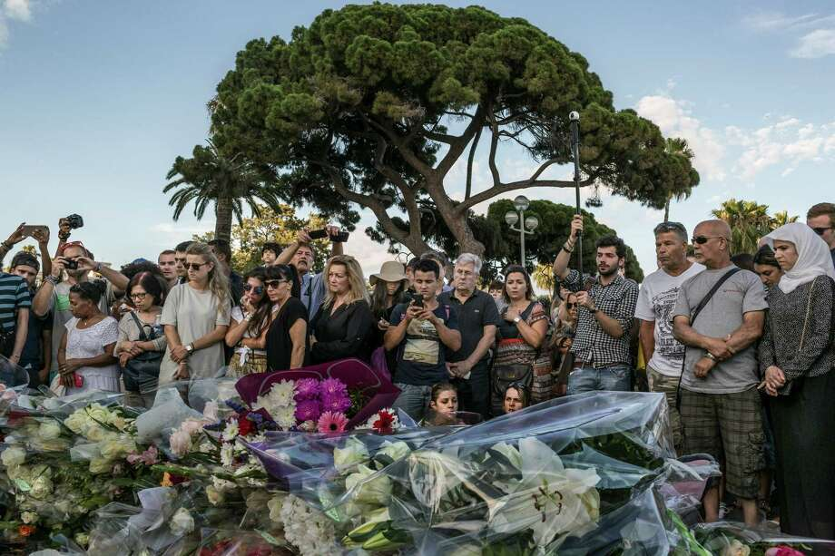 People stand at a makeshift memorial near the Promenade des Anglais, where a truck barreled for more than a mile through a crowd watching Bastille Day fireworks the night before, in Nice, France, July 15, 2016. The death toll from the terrorist attack rose to 84 on Friday, as the government raced to establish the attacker's identity, extended a national state of emergency and absorbed the shock of a third major terrorist attack in 19 months. (Mauricio Lima/The New York Times) Photo: MAURICIO LIMA, STR / NYT / NYTNS