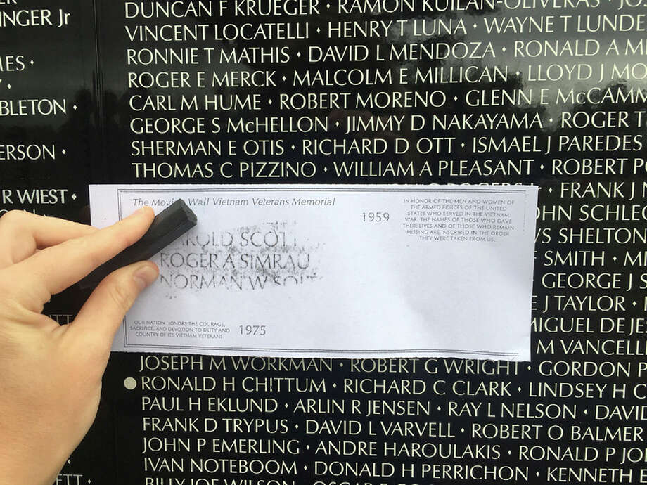 Reporter Jessica Haynes takes a rubbing of her great uncle's name during a visit to the Moving Wall, a half-size replica of the Vietnam Veterans Memorial that is currently in Sanford through July 18. Roger A. Simrau was the first casualty from Gladwin County and died in the Battle of Ia Drang, which was later commemorated in the book, 'We Were Soldiers Once... and Young,' and then a movie.