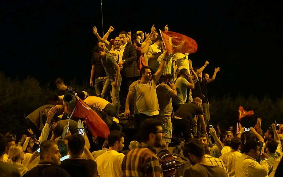 People gather on top of a Turkish armys tanks at Ataturk Airport on July 16, 2016 in Istanbul, Turkey. Istanbul's bridges across the Bosphorus, the strait separating the European and Asian sides of the city, have been closed to traffic. Reports have suggested that a group within Turkey's military have attempted to overthrow the government. Security forces have been called in as Turkey's Prime Minister Binali Yildirim denounced an 'illegal action' by a military 'group', with bridges closed in Istanbul and aircraft flying low over the capital of Ankara.  Photo: Defne Karadeniz, Getty Images