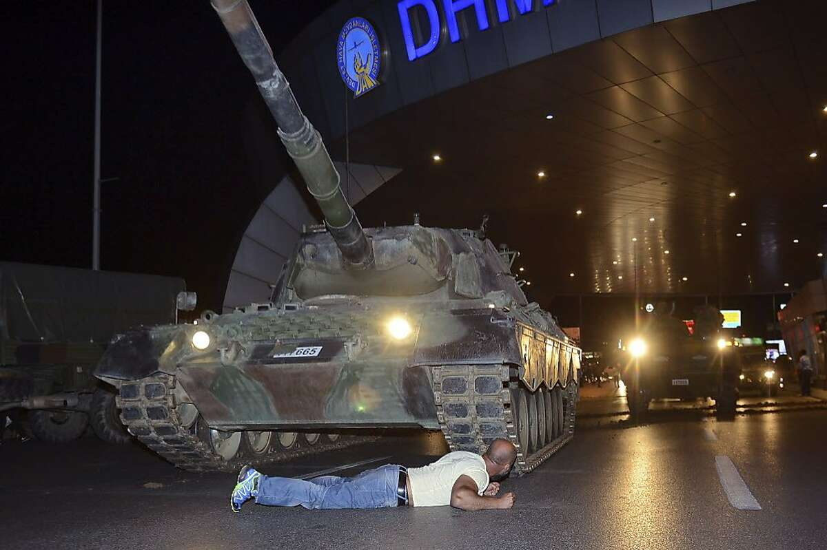 A man lays in front of a tank in the entrance to Istanbul's Ataturk airport, early Saturday, July 16, 2016. Members of Turkey's armed forces said they had taken control of the country, but Turkish officials said the coup attempt had been repelled early Saturday morning in a night of violence, according to state-run media.