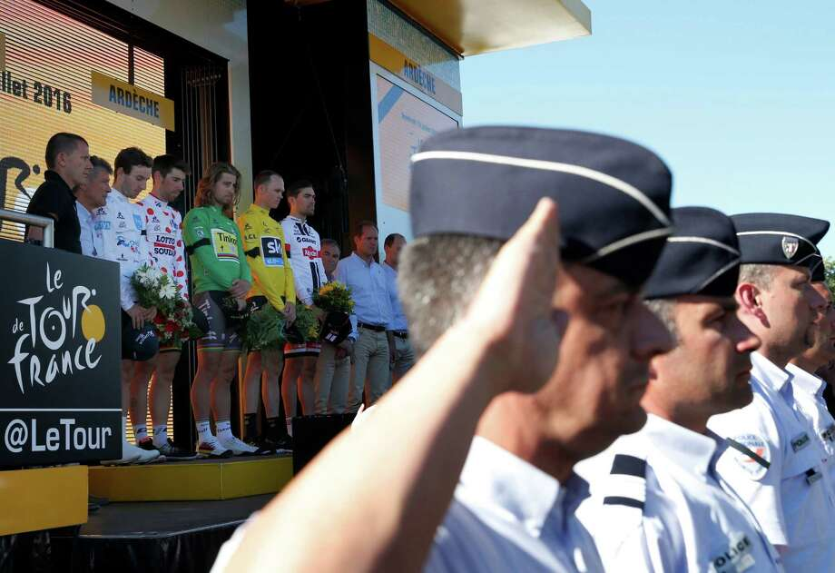Policemen and riders on the podium observe a minute of silence Friday to commemorate the victims of the Nice truck attack.  Photo: Christophe Ena, STF / AP