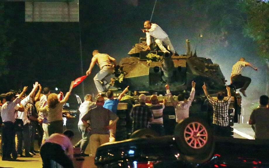 A tank moves into position as Turkish people attempt to stop it, in Ankara, Turkey, early Saturday. Members of Turkey's armed forces said they had taken control of the country Friday but the nation's leader later said the coup had been thwarted. Photo: STR / Copyright 2016 The Associated Press. All rights reserved. This material may not be published, broadcast, rewritten or redistribu