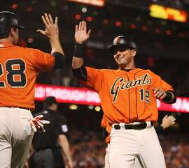 The San Francisco Giants' Joe Panik (12) high-fives Buster Posey, left, as they score on a three-run double by Brandon Belt against the Philadelphia Phillies in the seventh inning at AT&T Park in San Francisco, Calif., on Friday, June 24, 2016. (Jim Gensheimer/Bay Area News Group/TNS)