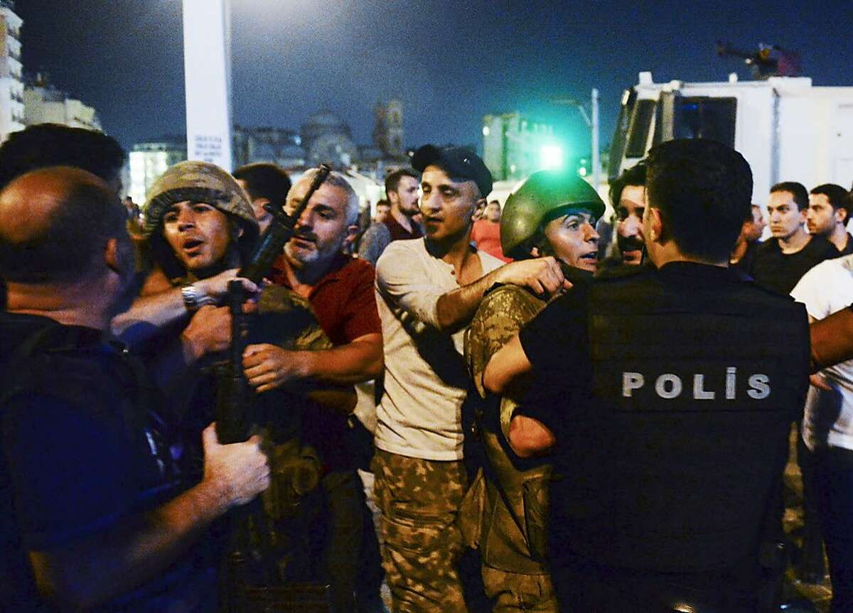 Turkish soldiers, arrested by civilians, are handed to police officers, in Istanbul's Taksim square, early Saturday, July 16, 2016. Members of Turkey's armed forces said they had taken control of the country, but Turkish officials said the coup attempt had been repelled early Saturday morning in a night of violence, according to state-run media.