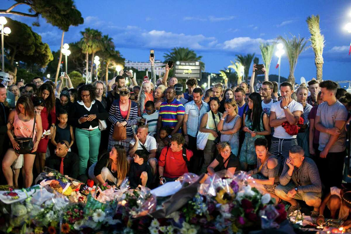 People gather at a makeshift memorial to honor the victims of an attack, near the area where a truck mowed through revelers in Nice, southern France, Friday, July 15, 2016. A large truck mowed through revelers gathered for Bastille Day fireworks in Nice, killing more than 80 people and sending people fleeing into the sea as it bore down for more than a mile along the Riviera city's famed waterfront promenade. (AP Photo/Laurent Cipriani) ORG XMIT: CIP115