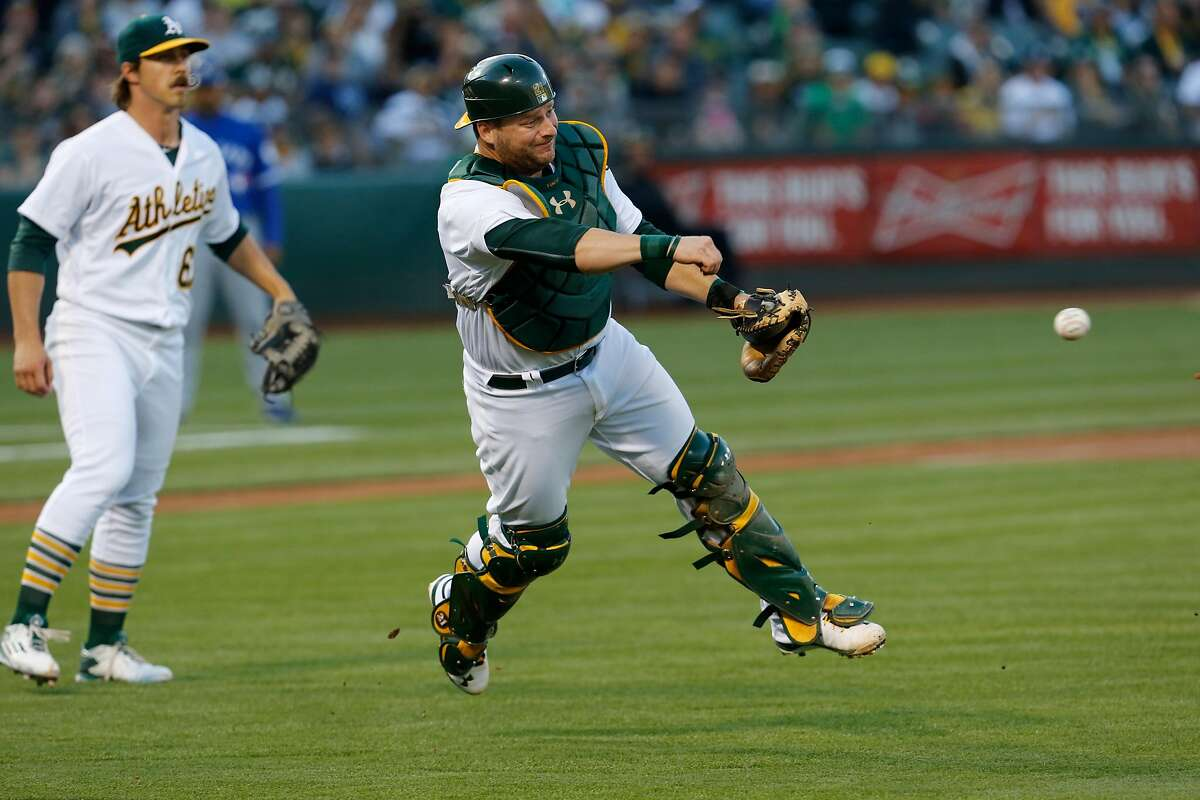 A's catch Stephen Vigt throws wide to first as the BLue Jay's Michael Saunders is safe at first in the first inng, as the Oakland Athletics take on the Toronto Blue Jays at the Oakland Alameda coliseum in Oakland, California, on Fri. July 15, 2016.