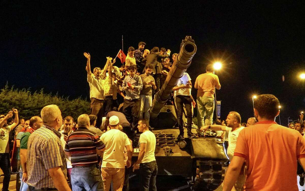 ISTANBUL, TURKEY - JULY 16: People gather on top of a Turkish armys tanks at Ataturk Airport on July 16, 2016 in Istanbul, Turkey. Istanbul's bridges across the Bosphorus, the strait separating the European and Asian sides of the city, have been closed to traffic. Reports have suggested that a group within Turkey's military have attempted to overthrow the government. Security forces have been called in as Turkey's Prime Minister Binali Yildirim denounced an 'illegal action' by a military 'group', with bridges closed in Istanbul and aircraft flying low over the capital of Ankara. (Photo by Defne Karadeniz/Getty Images) ORG XMIT: 655105703