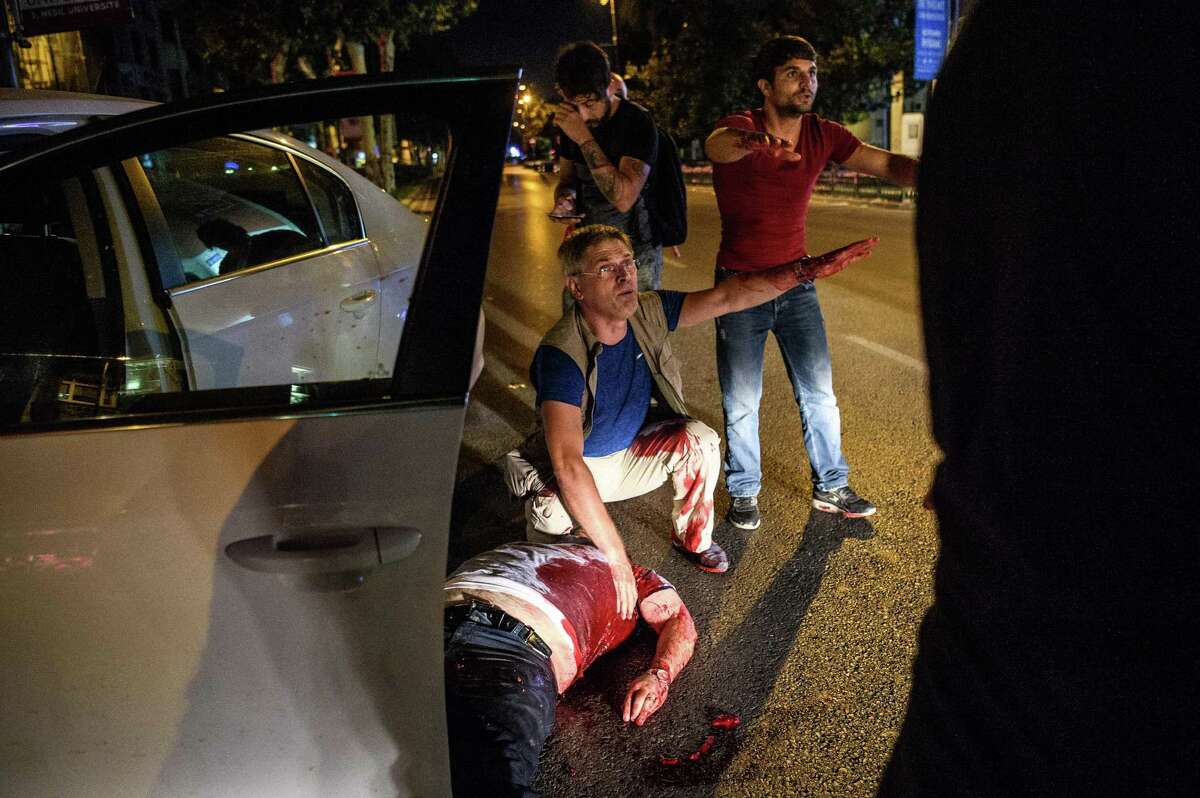 A man is shot in his car during clashes between Turkish solders and police near Taksim square in Istanbul on July 16, 2016. Turkish military forces on July 16 opened fire on crowds gathered in Istanbul following a coup attempt, causing casualties, an AFP photographer said. The soldiers opened fire on grounds around the first bridge across the Bosphorus dividing Europe and Asia, said the photographer, who saw wounded people being taken to ambulances. / AFP PHOTO / OZAN KOSEOZAN KOSE/AFP/Getty Images ORG XMIT: 7523