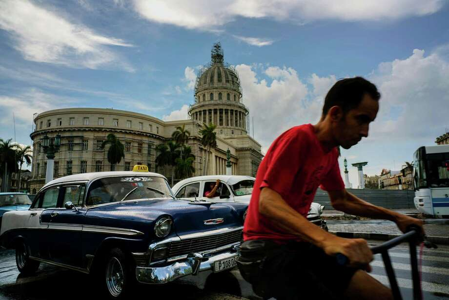 A bicyclist makes his way alongside taxi drivers Friday near the Cuban Capitol in Havana.  Photo: Ramon Espinosa, STF / Copyright 2016 The Associated Press. All rights reserved. This material may not be published, broadcast, rewritten or redistribu