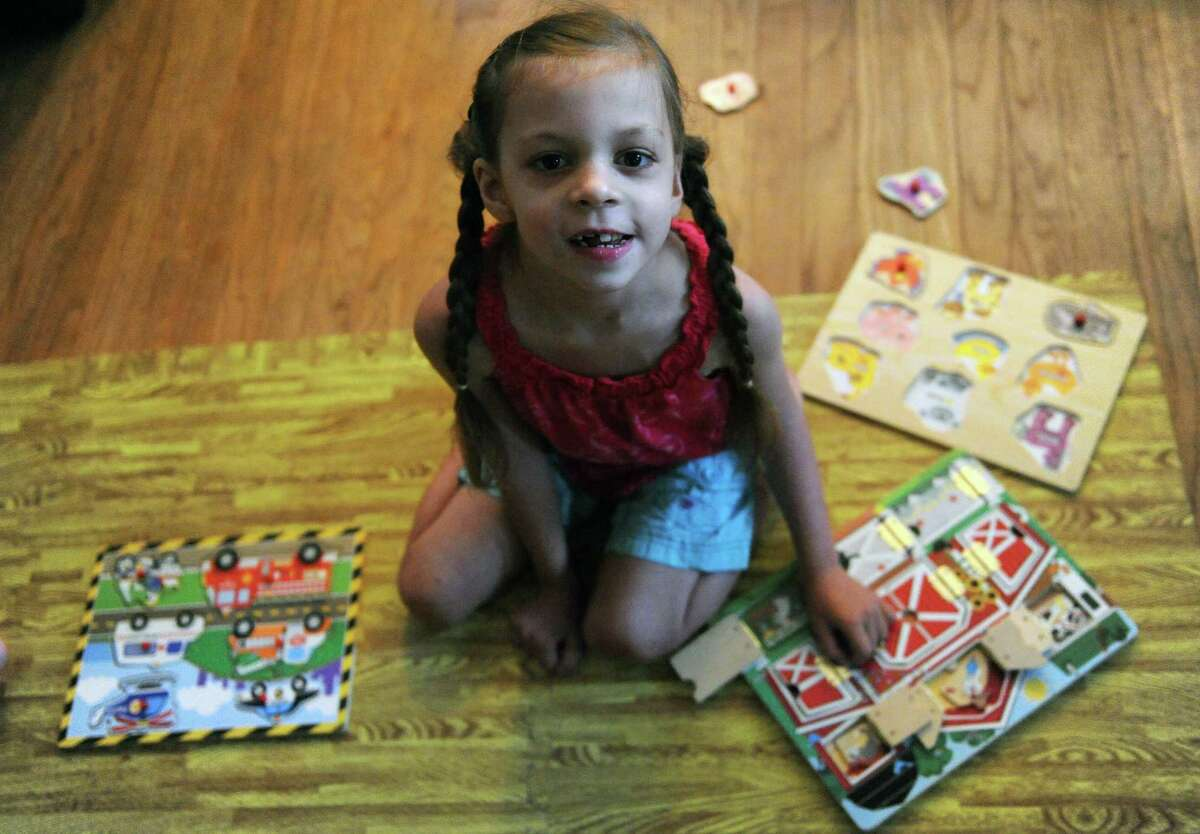 Seven-year-old Adrenne Kelly who has a rare form of epilepsy puts together puzzles on Wednesday July 13, 2016 in Albany , N.Y. Adrenne is in a medical marijuana drug trial at NYU. (Michael P. Farrell/Times Union)