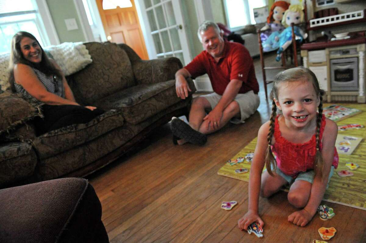 Seven-year-old Adrenne Kelly who has a rare form of epilepsy with her parents Bill and Kim Kelly at their home on Wednesday July 13, 2016 in Albany , N.Y. Adrenne is in a medical marijuana drug trial at NYU. (Michael P. Farrell/Times Union)