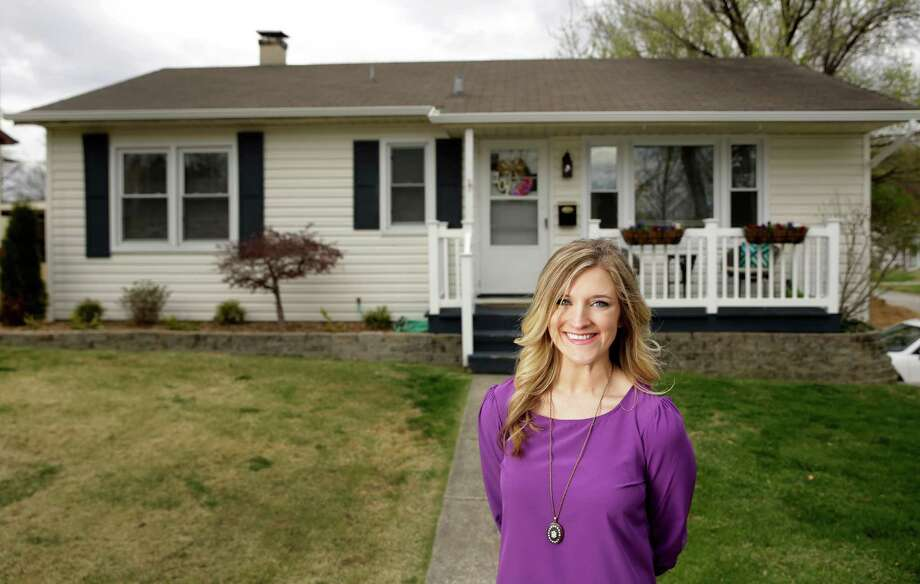 """In this Wednesday, March 30, 2016, photo, Kelsey Funk poses for a photo outside her home in St. Charles, Mo. Funk paid $113,000 for her three-bedroom home in suburban St. Louis about a year ago. """"I think what surprised me was how affordable it is,"""" Funk said. """"My monthly payment is way cheaper than rent. The cost to rent was generally $900 to $1,000. My mortgage is now $690. And it's something I own."""" (AP Photo/Jeff Roberson) Photo: Jeff Roberson, STF / Copyright 2016 The Associated Press. All rights reserved. This material may not be published, broadcast, rewritten or redistribu"""