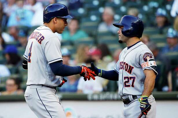 Houston Astros' George Springer, left, is greeted by Jose Altuve after Springer hit a solo home run during the first inning of a baseball game against the Seattle Mariners, Friday, July 15, 2016, in Seattle. (AP Photo/Ted S. Warren)