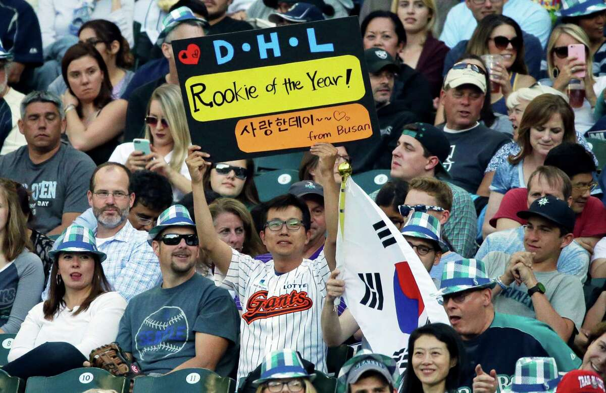 A fan in the stands holds a sign calling for Seattle Mariners first baseman Dae-Ho Lee to be named rookie of the year, during a baseball game between the Mariners and the Houston Astros, Friday, July 15, 2016, in Seattle. (AP Photo/Ted S. Warren)