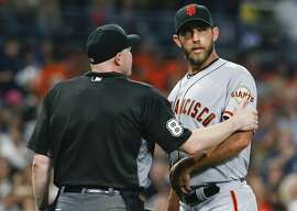 Home plate umpire Mike Estabrook puts a hand on the warm of San Francisco Giants pitcher Madison Bumgarner after the top half of the fifth inning of the Giants' baseball game against the San Diego Padres on Friday, July 15, 2016, in San Diego. (AP Photo/Lenny Ignelzi)