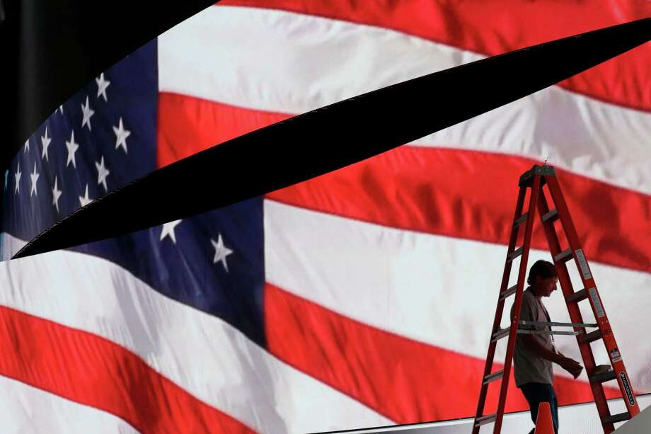 Adam West prepares to move a ladder from in front of the stage screen that displays an American flag as preparations continue for the Republican National Convention, Friday, July 15,2016, at the Quicken Loans Arena in Cleveland.  In political battleground states across the country, a sense of anger and anxiety is inflicting voters as the Republican and Democratic conventions formally kick off the 2016 general election. Photo: Alex Brandon, AP / Copyright 2016 The Associated Press. All rights reserved. This material may not be published, broadcast, rewritten or redistribu