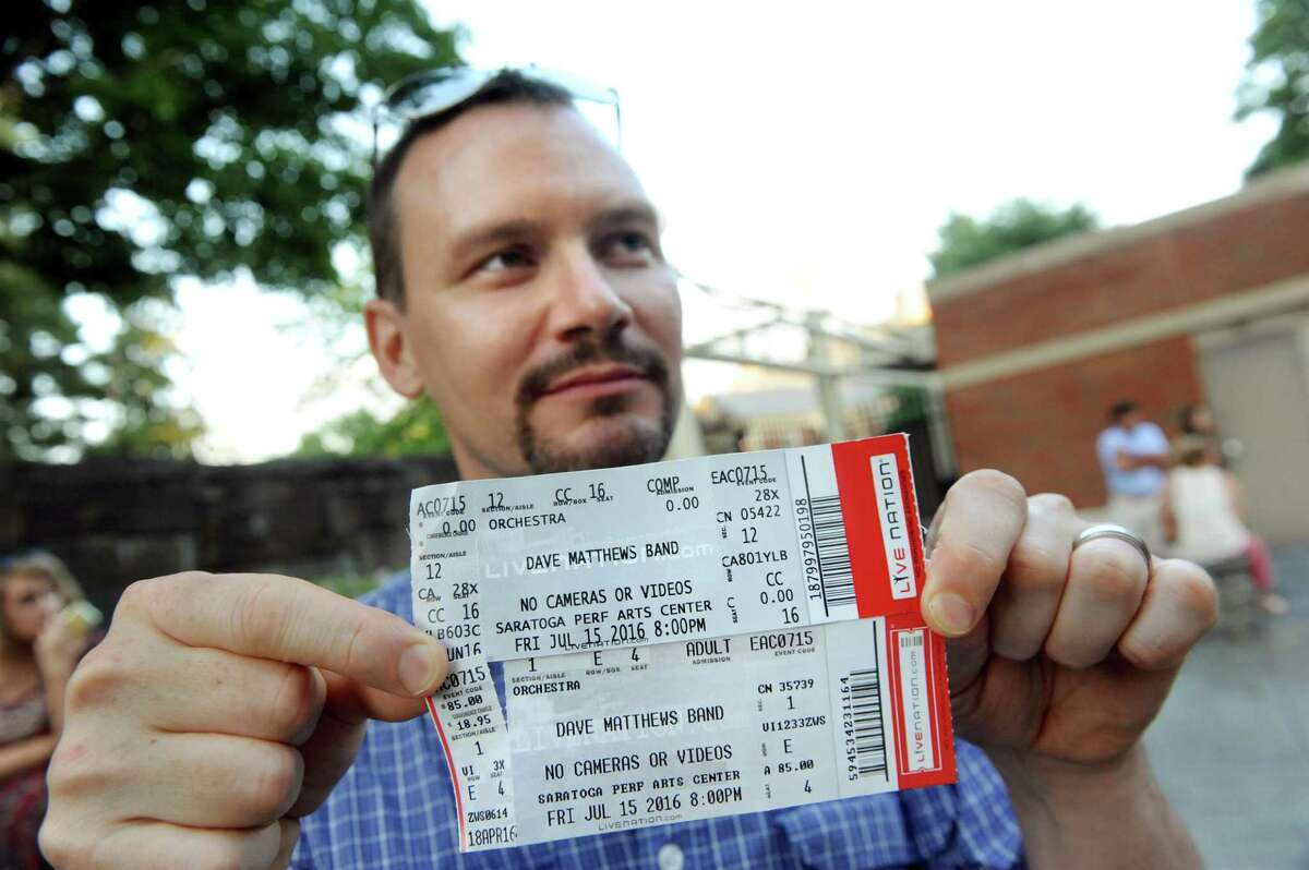 Ed Fredrich of Malta holds up a real ticket, top, and a bogus ticket for the Dave Matthews Band on Friday, July 15, 2016, at Saratoga Performing Arts Center in Saratoga Springs, N.Y. (Cindy Schultz / Times Union)