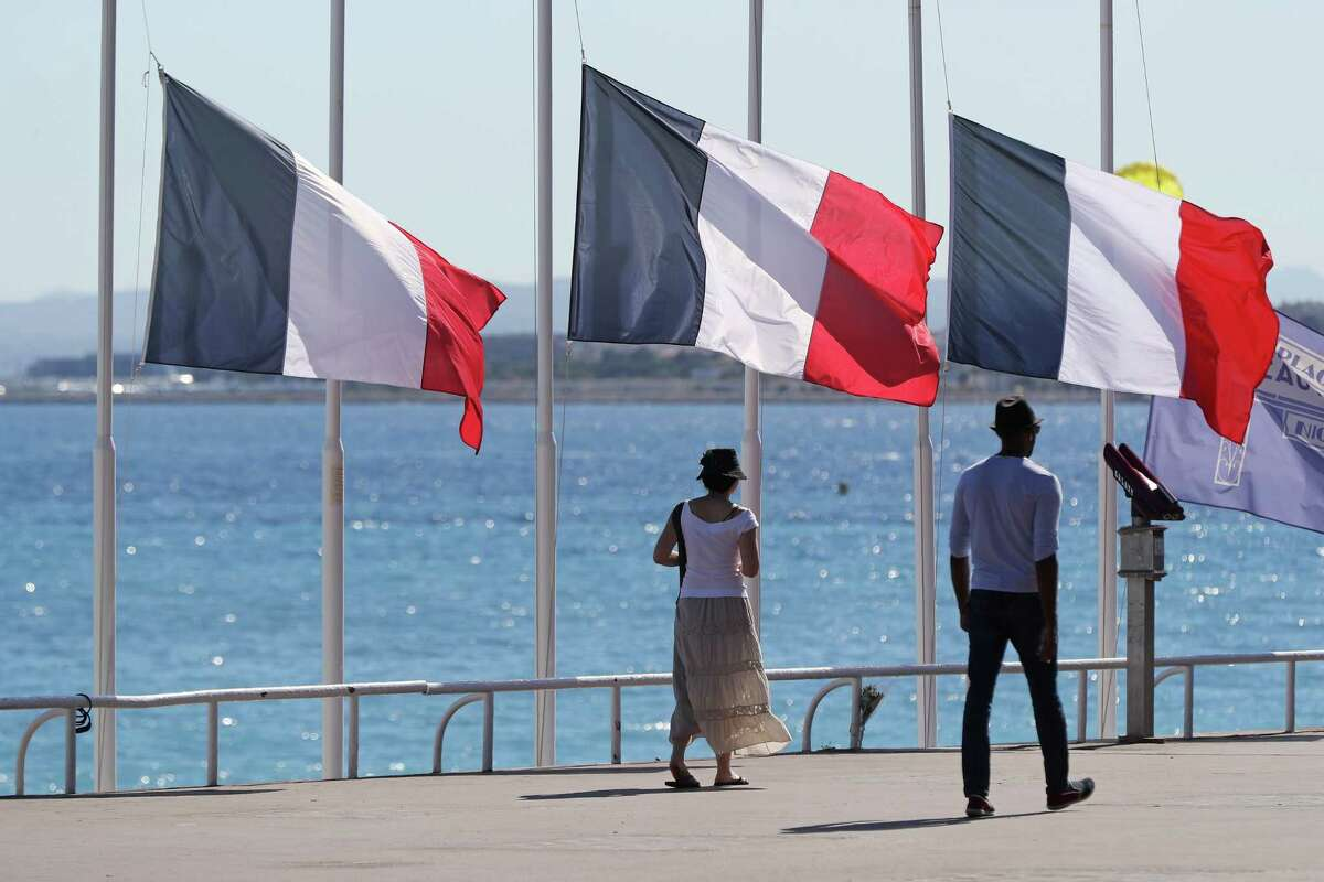 People pass French flags lowered at half-mast in Nice on July 16, 2016, following the deadly Bastille Day attack. The Islamic State group claimed responsibility for the truck attack that killed 84 people in Nice on France's national holiday, a news service affiliated with the jihadists said on July 16. Tunisian Mohamed Lahouaiej-Bouhlel, 31, smashed a 19-tonne truck into a packed crowd of people in the Riviera city celebrating Bastille Day -- France's national day. / AFP PHOTO / Valery HACHEVALERY HACHE/AFP/Getty Images