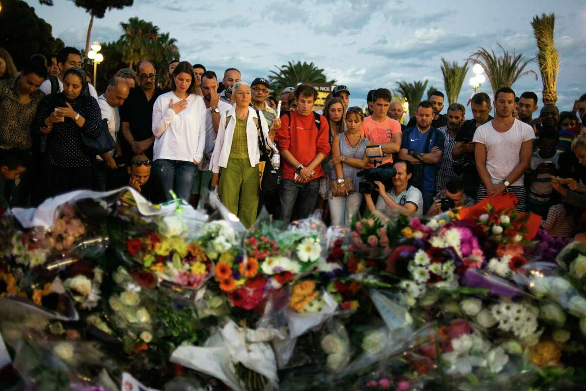 People mourn at a makeshift memorial on the Promenade des Anglais, where a man drove a 19-ton truck through the Bastille Day fireworks crowds, killing 84 and leaving hundreds more wounded the night before in Nice, France, July 15, 2016. Absorbing the shock of a third major terrorist attack in 19 months, France extended a national state of emergency by three months. (Dmitry Kostyukov/The New York Times) ORG XMIT: XNYT106