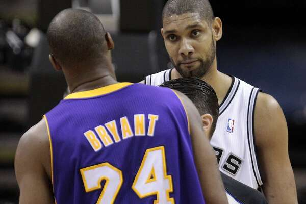 San Antonio Spurs' Tim Duncan, right, stares down Los Angeles Lakers' Kobe Bryant after Bryant and San Antonio Spurs' George Hill exchanged words during the second quarter of an NBA basketball game Tuesday, Dec. 28, 2010, in San Antonio. (AP Photo/Eric Gay)