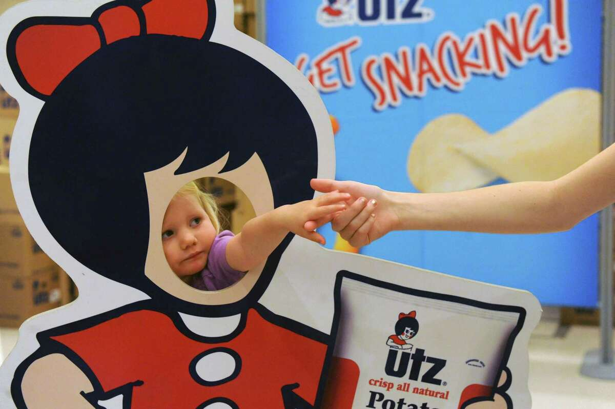 Two-year-old Phoebe Johnson visting relatives in Saratoga stands behind a UTZ girl cutout during the inaugural Chip Festival at the City Center on Saturday July 16, 2016 in Saratoga Springs, N.Y. (Michael P. Farrell/Times Union)