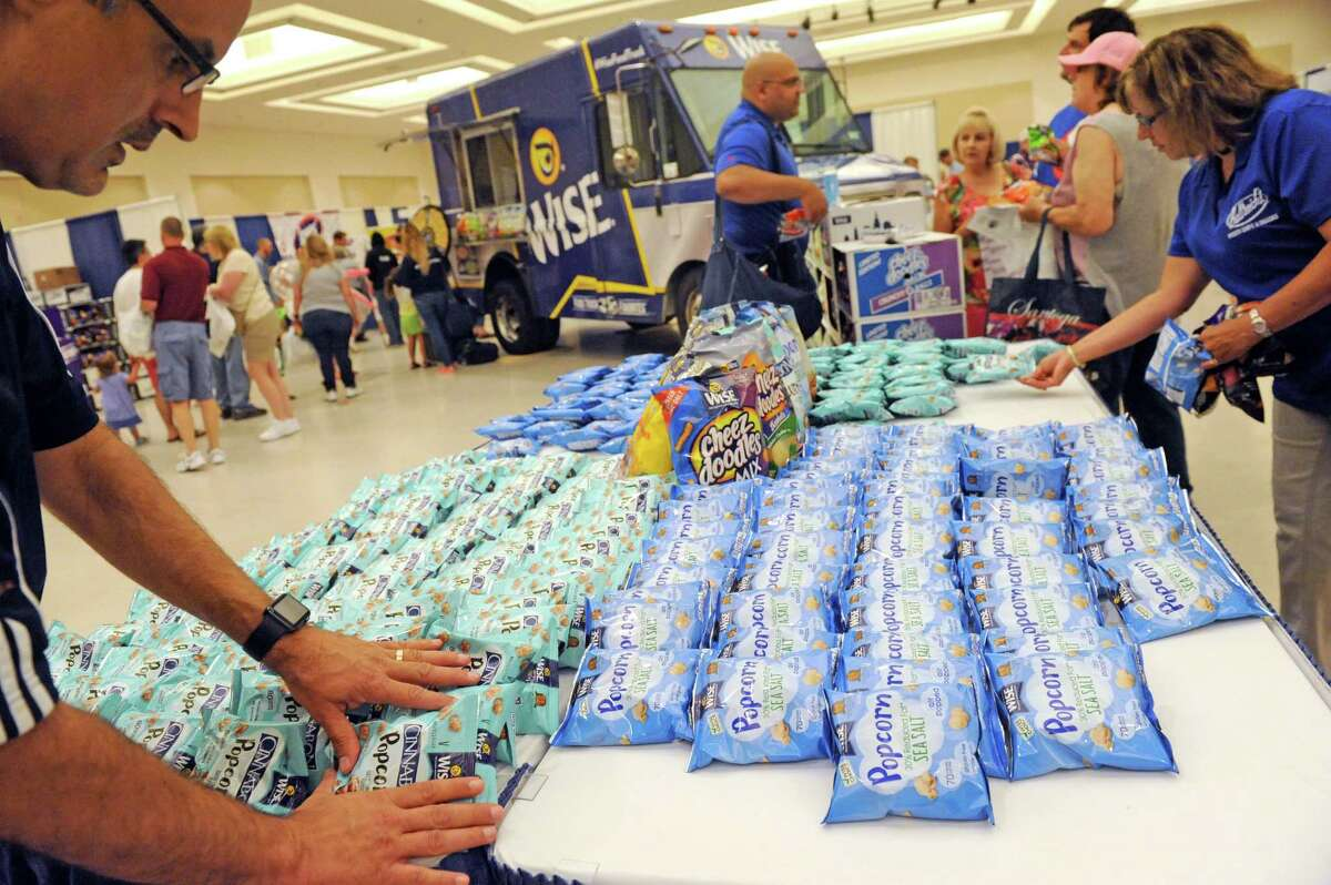 Arturo Chavez, left, marketing director for Wise, keeps the free product samples stocked during the inaugural Chip Festival at the City Center on Saturday July 16, 2016 in Saratoga Springs, N.Y. (Michael P. Farrell/Times Union)