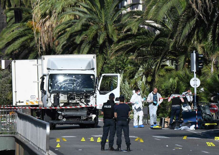 """Forensics officers and policemen look for evidences near a truck on the Promenade des Anglais seafront in the French Riviera town of Nice on July 15, 2016, after it drove into a crowd watching a fireworks display. An attack in Nice where a man rammed a truck into a crowd of people left 84 dead and another 18 in a """"critical condition"""", interior ministry spokesman Pierre-Henry Brandet said Friday. An unidentified gunman barrelled the truck two kilometres (1.3 miles) through a crowd that had been enjoying a fireworks display for France's national day before being shot dead by police.  / AFP PHOTO / ANNE-CHRISTINE POUJOULATANNE-CHRISTINE POUJOULAT/AFP/Getty Images Photo: ANNE-CHRISTINE POUJOULAT, Staff / AFP/Getty Images / AFP or licensors"""