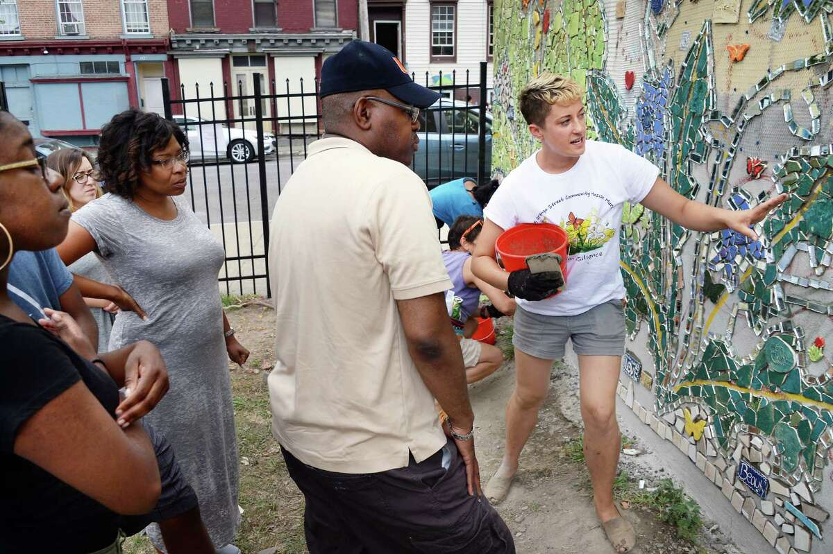 Arts Center instructor Jillian Hirsch, right, directs volunteers working on a mosaic mural on the side of the Community Loan Fund building at 255 Orange Street Saturday July 16, 2016 in Albany, NY. The Community Loan Fund of the Capital Region and the Albany Center for Economic Success partnered to create the urban resilience themed mural. (John Carl D'Annibale / Times Union)