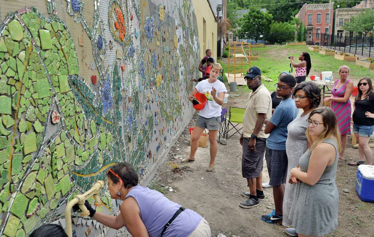 Arts Center instructor Jillian Hirsch, center, directs volunteers working on a mosaic mural on the side of the Community Loan Fund building at 255 Orange Street Saturday July 16, 2016 in Albany, NY. The Community Loan Fund of the Capital Region and the Albany Center for Economic Success partnered to create the urban resilience themed mural. (John Carl D'Annibale / Times Union)