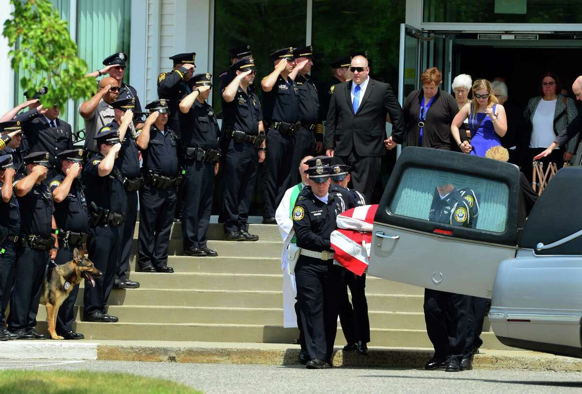Police officers stand at attention and salute as the casket for retired Bethel police officer Kevin Kennedy is taken to an awaiting hearse during a funeral service which was held at Immanuel Lutheran Church in Danbury, Conn., on Saturday July 16, 2016. The burial took place at Immanuel Lutheran Cemetery following the service. Police said Kennedy, who retired last year, shot himself after authorities were called to the Plumtree Heights Condo Complex where he resided in Bethel.