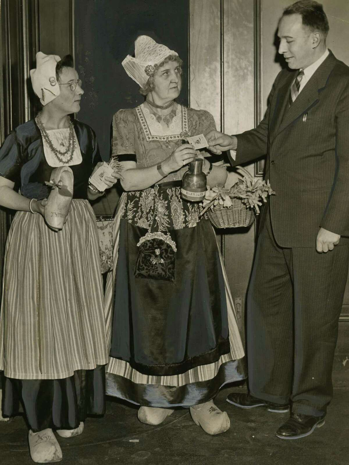 Mrs. Frank Spoor, left, and Mrs. John van Galen, center, sell a Nijmegen campaign tag to Mayor Erastus Corning collection, right, at City Hall in Albany on April 16, 1947. (Times Union archive photo)