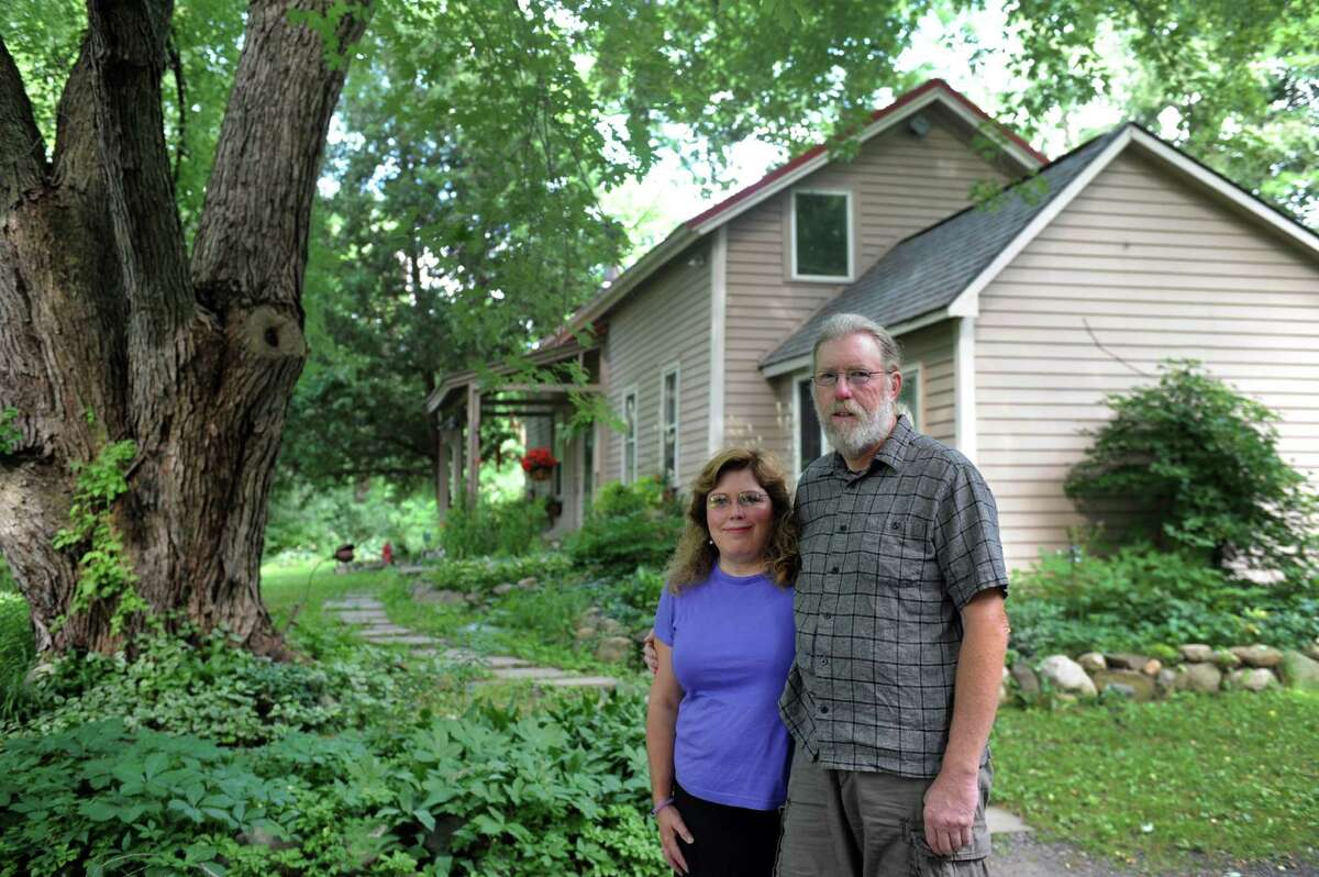 Sue Thompson and Tom Schweder in front of their English Road home on Saturday July 16, 2016 in Round Lake, N.Y. (Michael P. Farrell/Times Union)