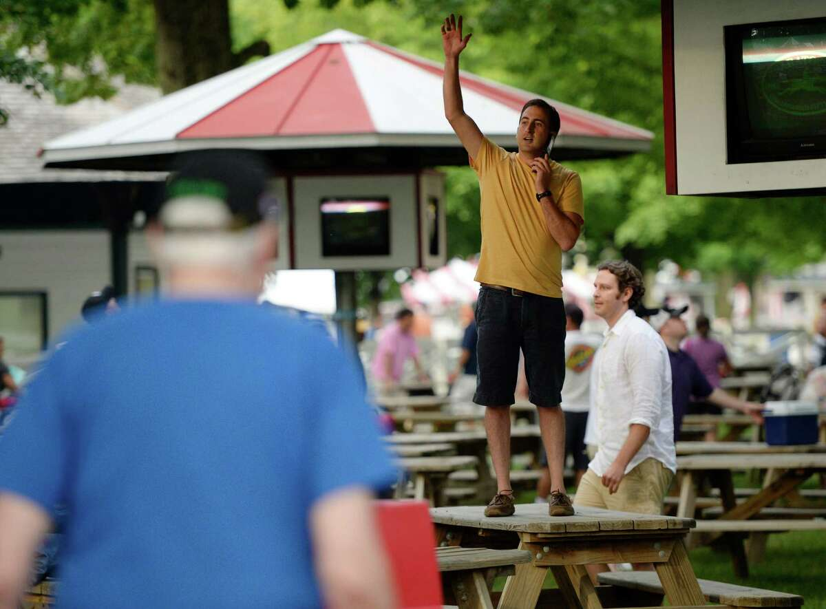 Racing patron Jake Keck stands on a picnic table to secure their places in the picnic area on opening day July 19, 2013, at Saratoga Race Course in Saratoga Springs, N.Y. (Skip Dickstein/Times Union)