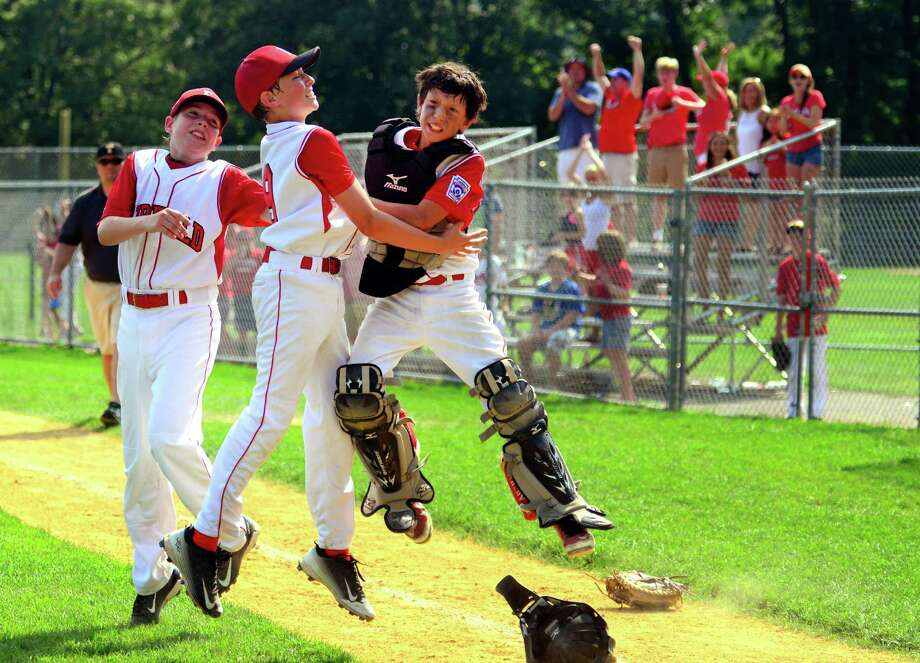 Fairfield American pitcher Jack Gremse, center, leaps into the air with catcher Matt Vivona to celebrate the team's win over Trumbull National in District 2 little league tournament action at Unity Park in Trumbull, Conn. on Saturday July 15, 2016. Photo: Christian Abraham / Hearst Connecticut Media / Connecticut Post
