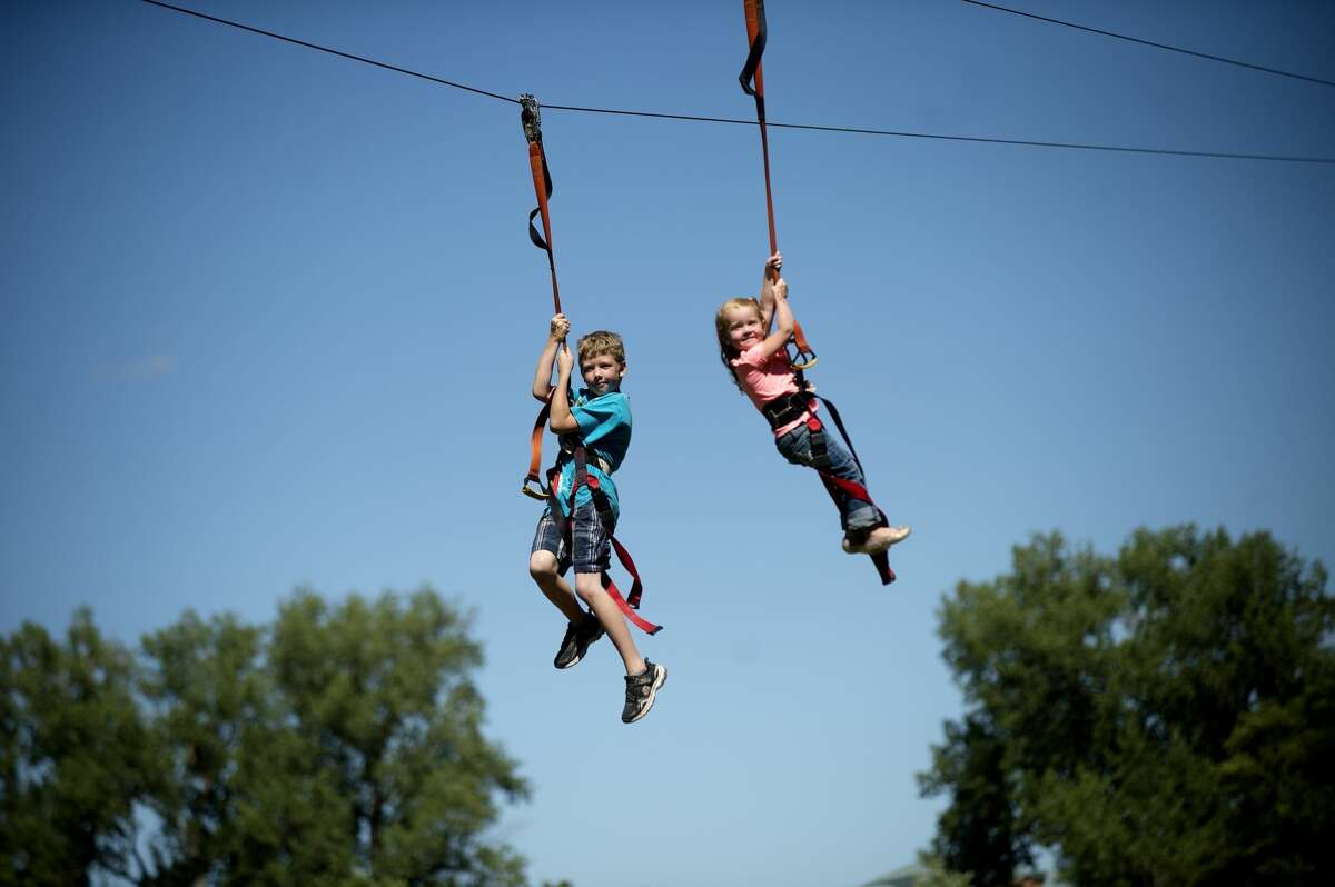 Collin Nephew, left, 8, and his sister Joslynn ride on the zip line during RiverDays at Chippewassee Park in 2016. (Nick King/Daily News file)