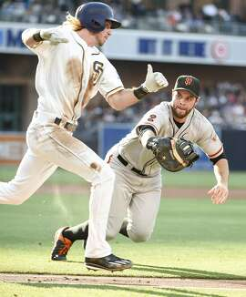 SAN DIEGO, CALIFORNIA - JULY 16: Brandon Belt #9 of the San Francisco Giants dives as he makes the tag on Travis Jankowski #16 of the San Diego Padres during the second inning of a baseball game at PETCO Park on July 16, 2016 in San Diego, California. Jankowski was tagged out on his way to first base. (Photo by Denis Poroy/Getty Images)