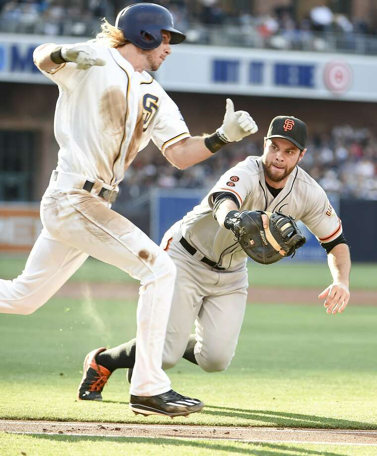 Brandon Belt #9 of the San Francisco Giants dives as he makes the tag on Travis Jankowski #16 of the San Diego Padres during the second inning of a baseball game at PETCO Park on July 16, 2016 in San Diego, California. Jankowski was tagged out on his way to first base. Photo: Denis Poroy, Getty Images