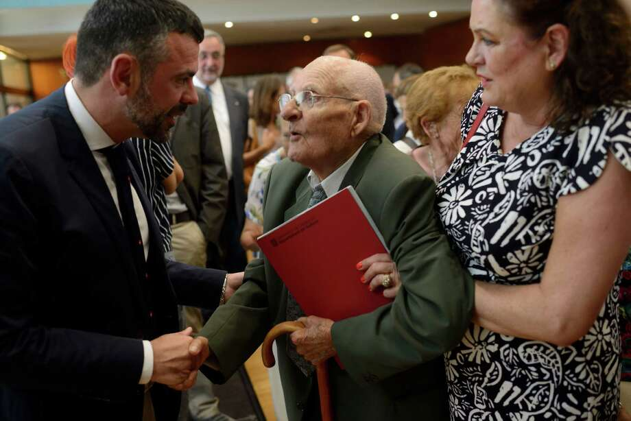 Family booklets and photos seized during the Spanish Civil War are returned to Pere Bartolomé at a ceremony this month in Sant Cugat, Spain. The 93-year-old remembers the day Gen. Francisco Franco's soldiers ransacked his village.  Photo: SAMUEL ARANDA, STR / NYTNS