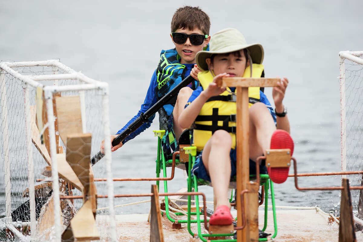 Kids show off their pedal-powered milk carton boat as part of the parade of boats during Seafair Derby Day at Green Lake Park on Saturday, July 16, 2016.