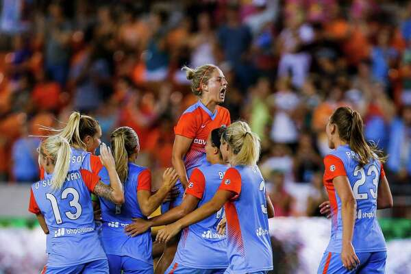 Houston Dash defender Ellie Brush (8) jumps into a pile of players after forward Kealia Ohai (7) scored in the second half s the Houston Dash beat the Portland Thorns FC 3-0 at BBVA Compass Stadium Saturday, July 16, 2016.
