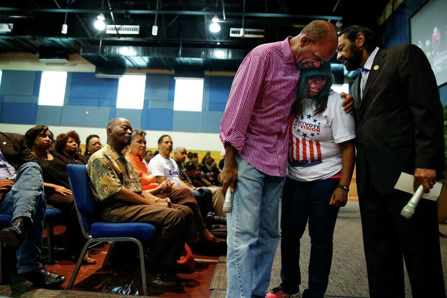 Windsor Village United Methodist Church senior pastor Kirbyjon H. Caldwell, left, comforts Demetria Smith, center, alongside Congressman Al Green, right, after Smith delivered emotional remarks to a panel of members of the law enforcement community at a Courageous Conversation town hall to address police violence against minority communities at The Kingdom Builder's Center Saturday, July 16, 2016. ( Michael Ciaglo / Houston Chronicle ) Photo: Michael Ciaglo, Staff / © 2016  Houston Chronicle