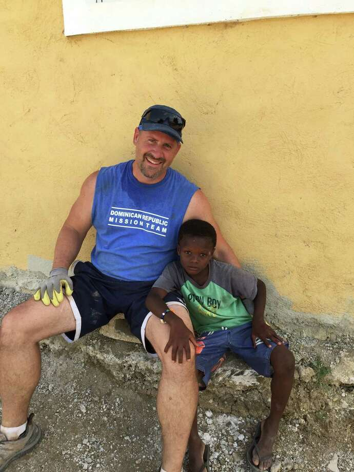 Brian Wallace, creative arts director for the Diocese of Bridgeport, with the member of a family his church group helped while on a mission trip to Dominican Republic. The republic is considered a hot spot for mosquito-borne Zika virus, as 16 of 27 Connecticut residents who tested positived for the illness traveled there. Photo: Contributed (By Brian Wallace)