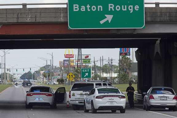 Baton Rouge Police block Airline Highway after police were shot in Baton Rouge, La., Sunday, July 17, 2016.  At least three officers are confirmed dead and at least three others wounded after the shooting, a sheriff's office spokeswoman said Sunday. One suspect is dead and law enforcement officials believe two others are still at large, the spokeswoman said.  (AP Photo/Max Becherer)