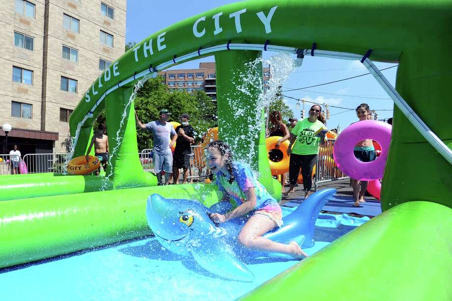 12-year old Amanda Asei rides a shark down the start of Slide the City, a 1,000 foot water slide on Hoyt Street in downtown Stamford on Sunday, July 17, 2016. Photo: Michael Cummo, Hearst Connecticut Media / Stamford Advocate